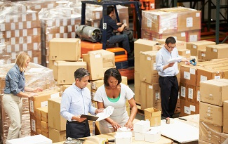 Male And Female Workers In Warehouse Preparing Goods For Dispatch